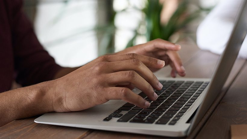 person on computer writing a blog